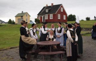 Annríki - Þjóðbúningar og skart. Hildur aðstoðrar við húfuuppsetningu. Hópur kvenna í íslenskum búningum.